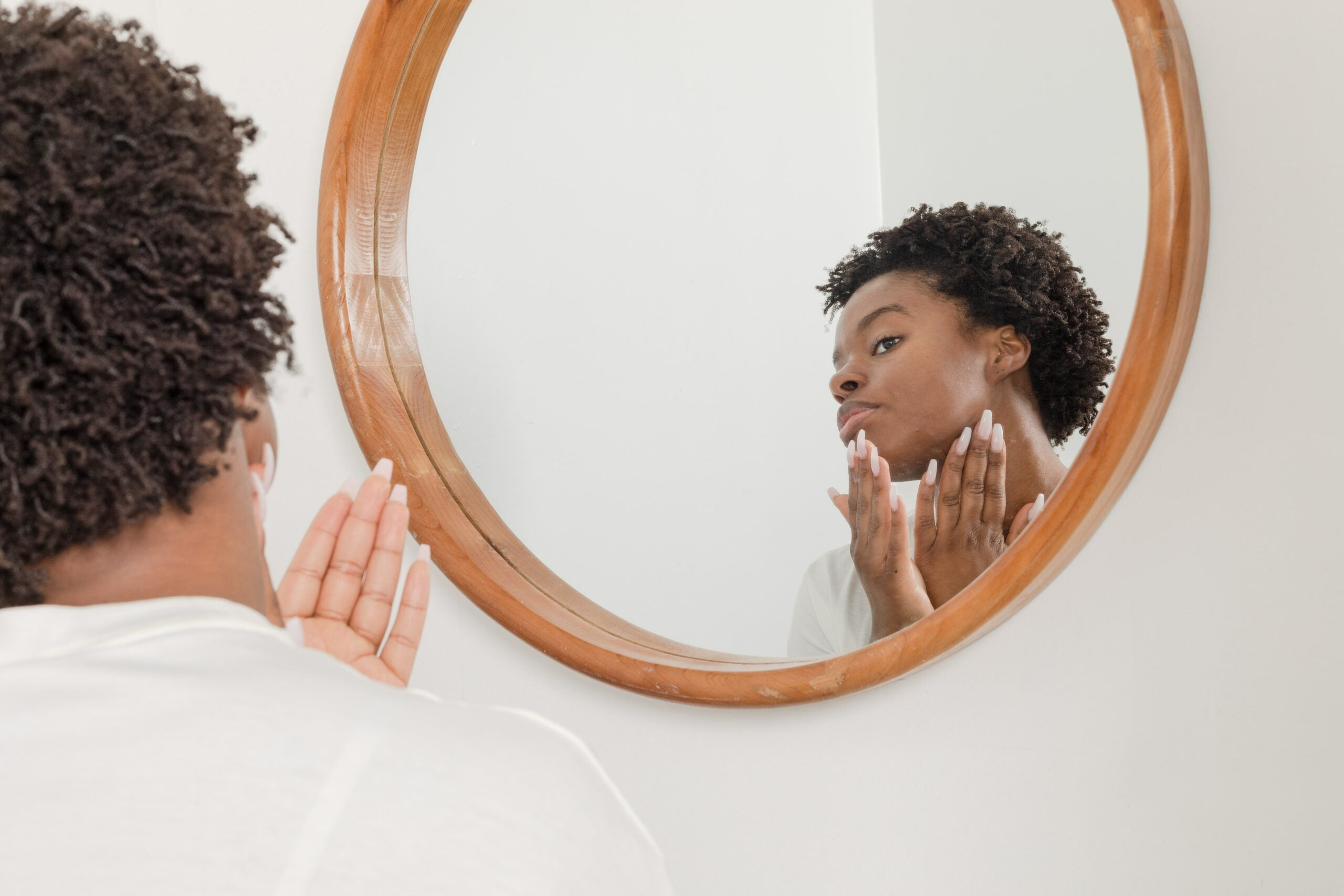 Woman applying lotion in mirror