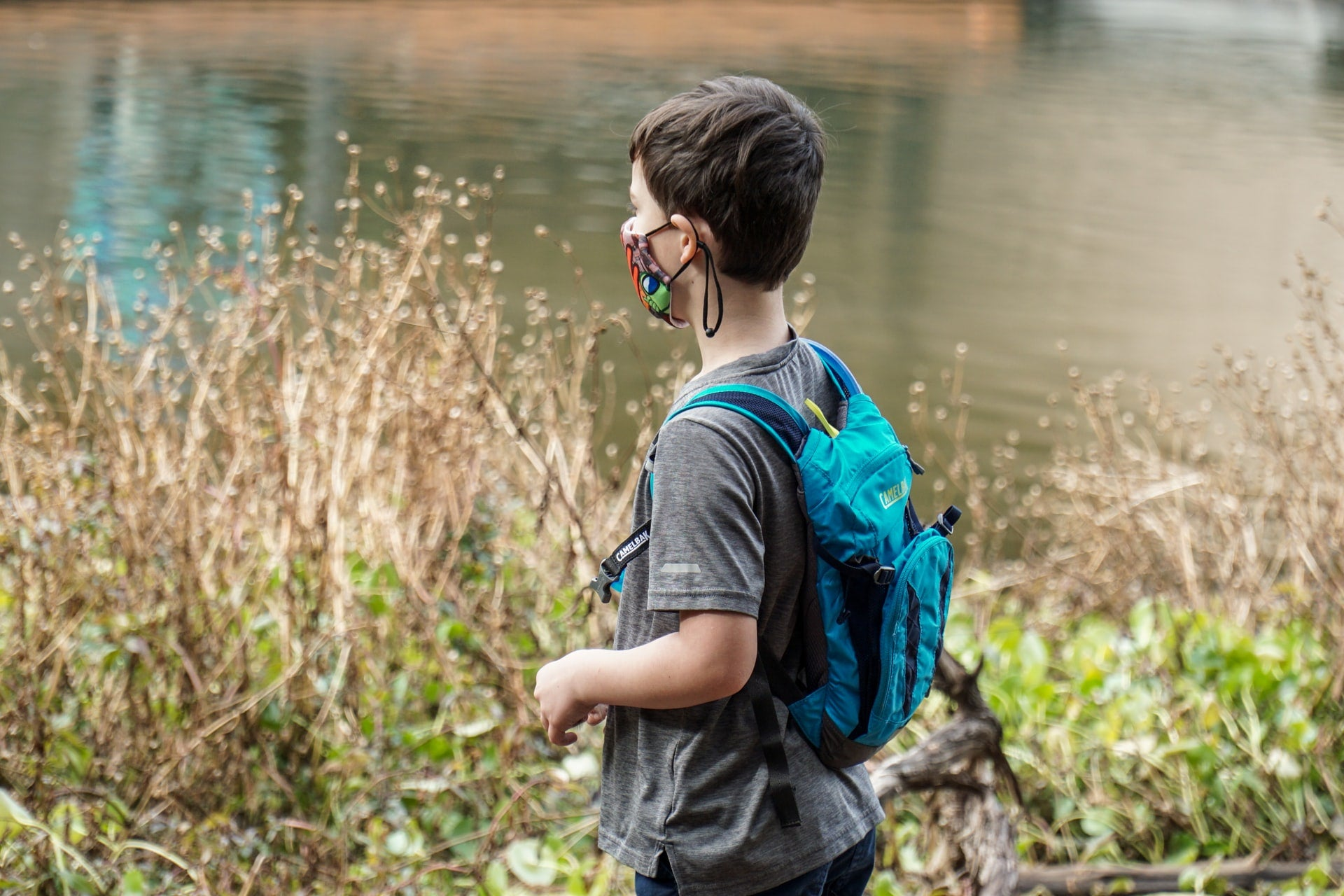 Kid with mask and backpack next to a pond