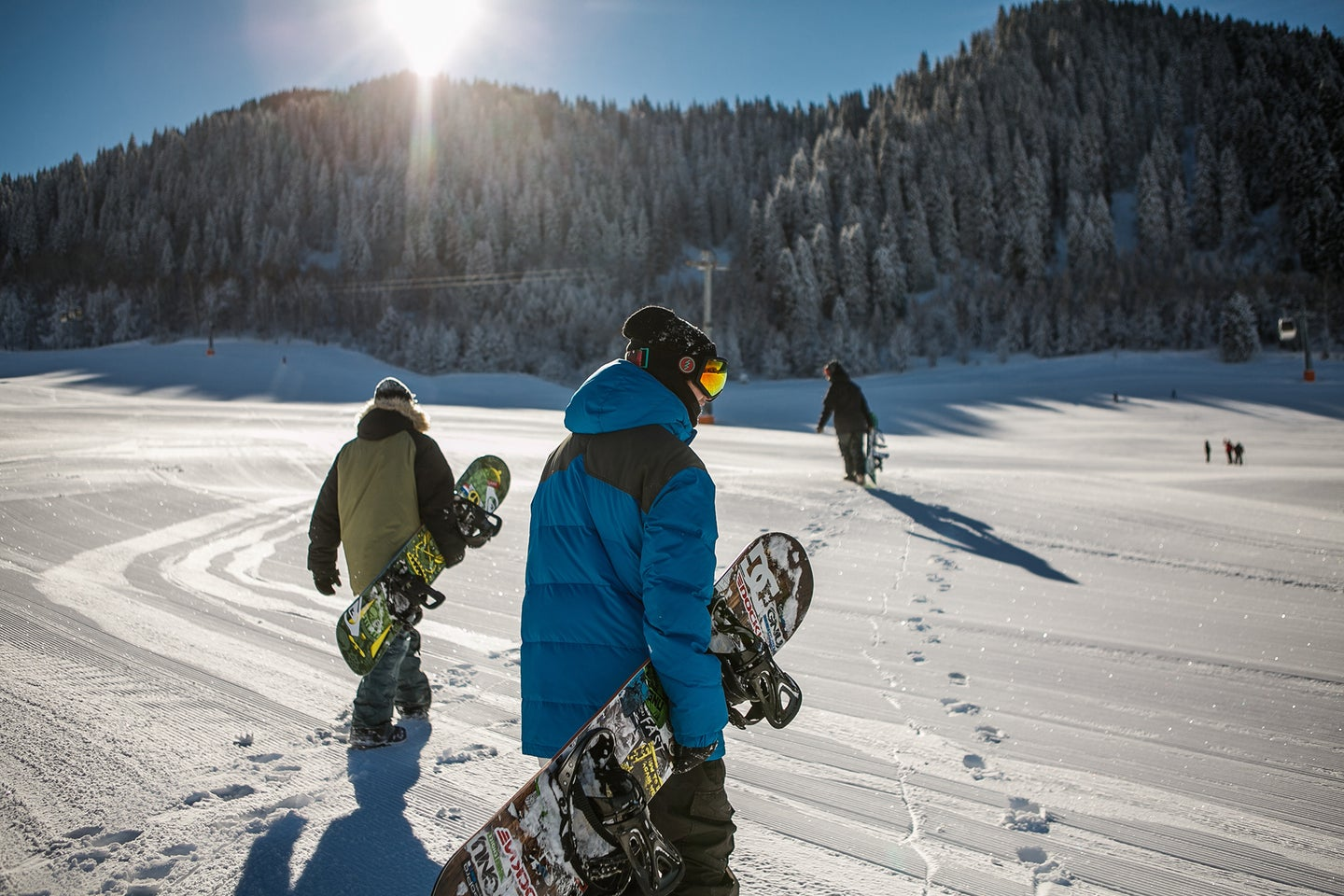 three people with snowboards walking on a snowy moutain