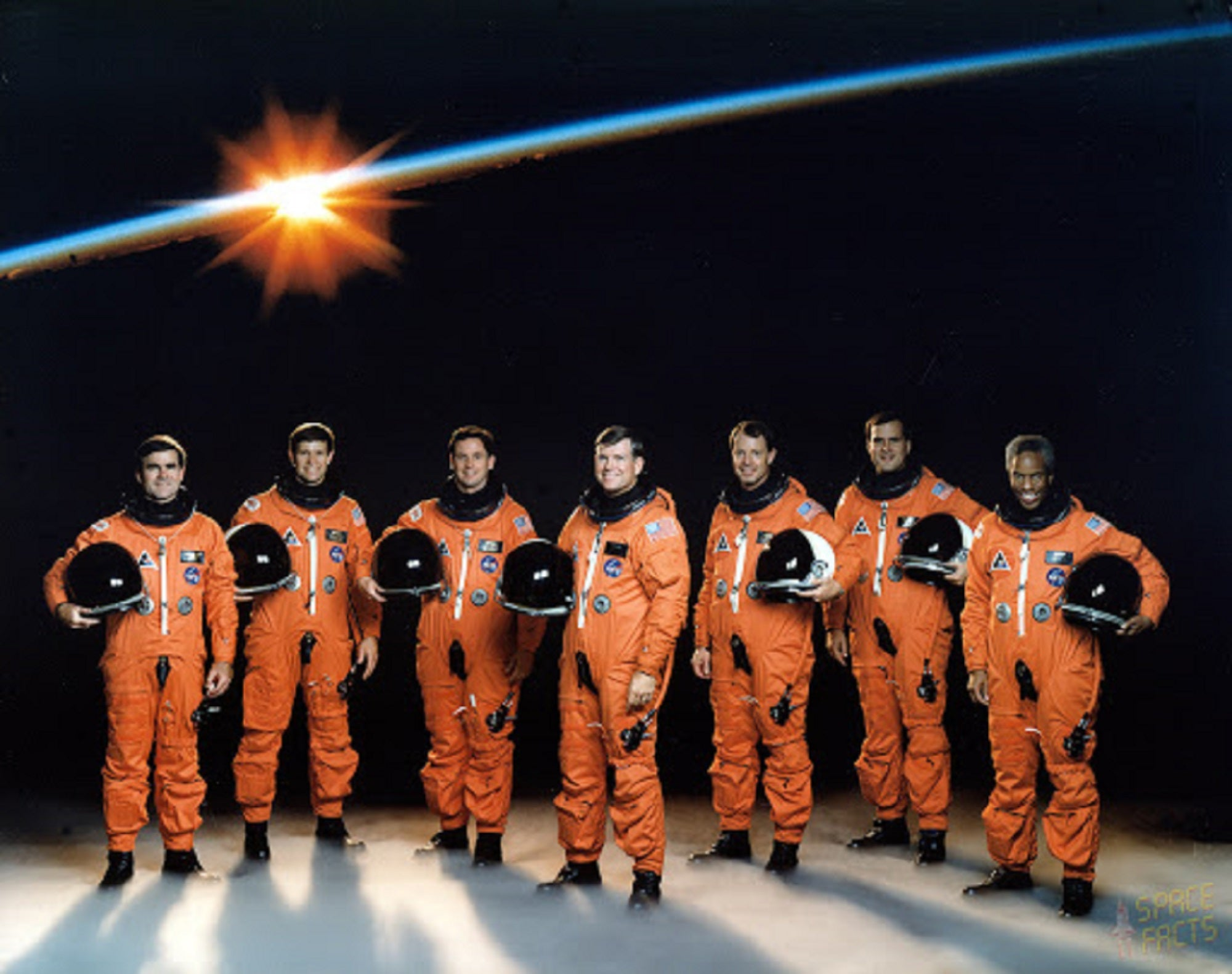 The NASA STS-39 shuttle crew in orange astronaut suits on a space backdrop