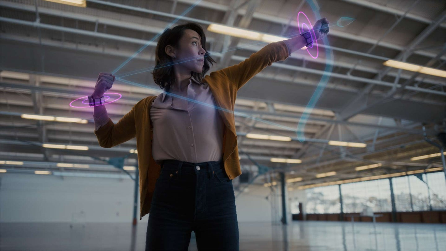 A woman pulling back a virtual bow to shoot an arrow while wearing Facebook's prototype haptic feedback wrist devices