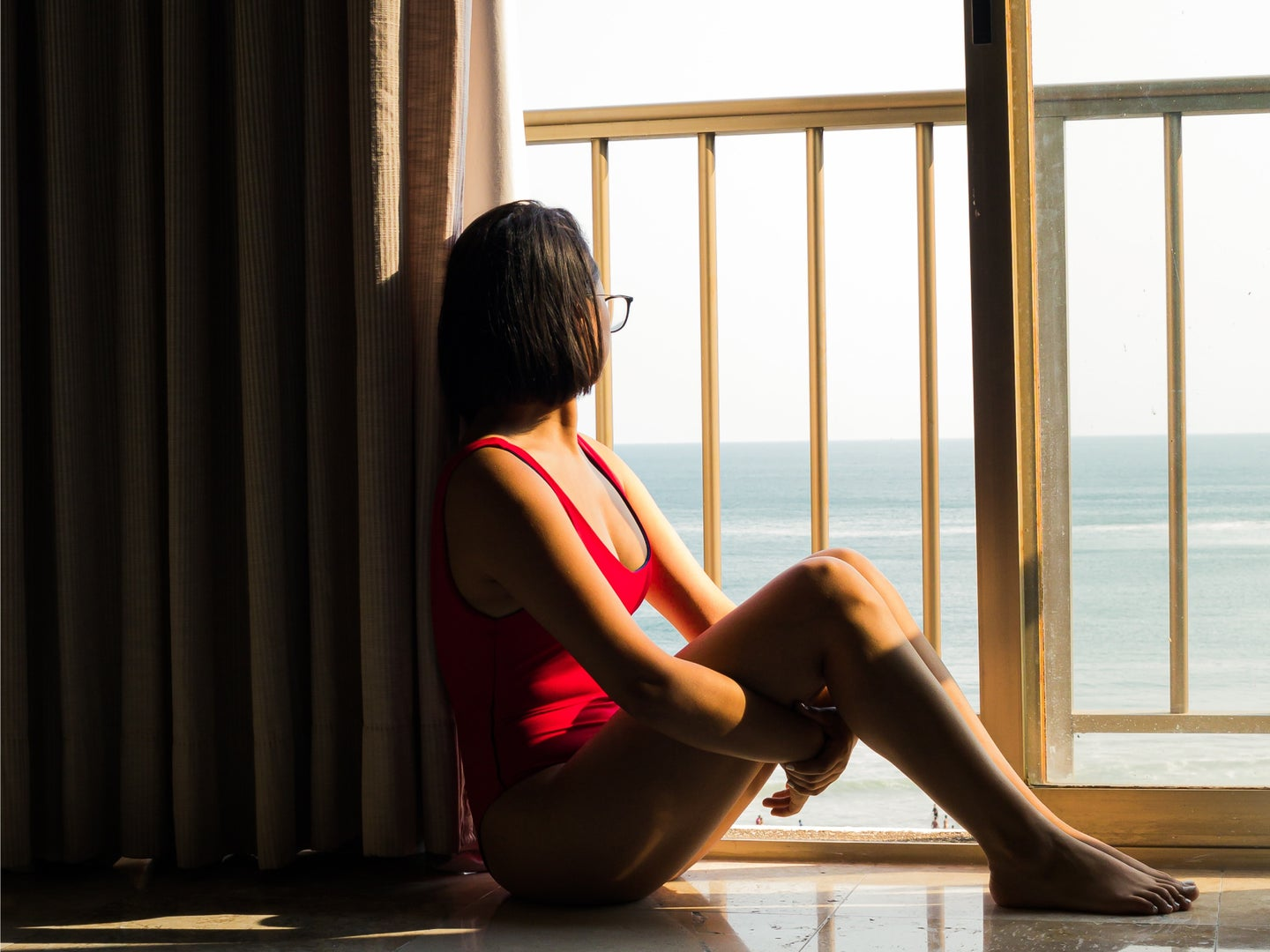 A woman in a red bathing suit sitting on the floor by a sliding glass door, staring at the ocean outside.