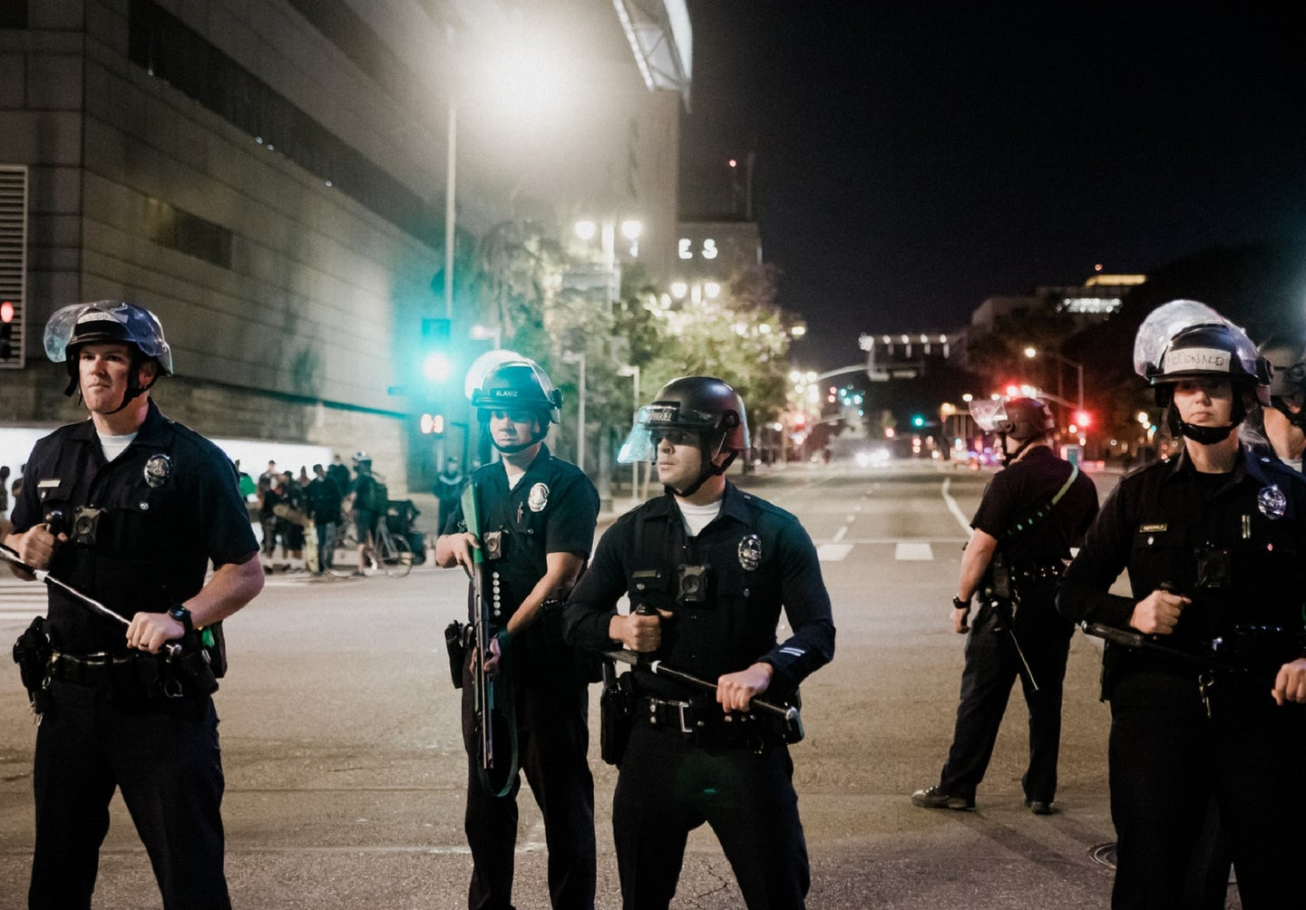 LAPD officers with batons and helmets on the street at night