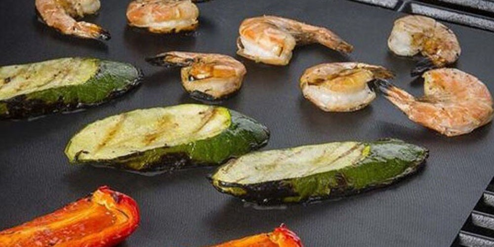zucchini, shrimp, and peppers on a grill mat
