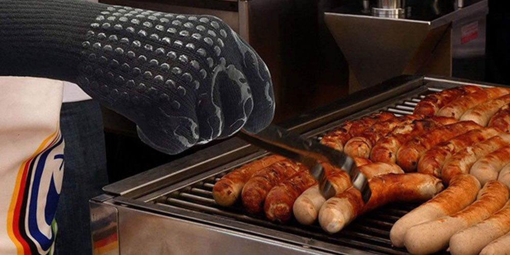 person turning over a sausage on grill with tongs