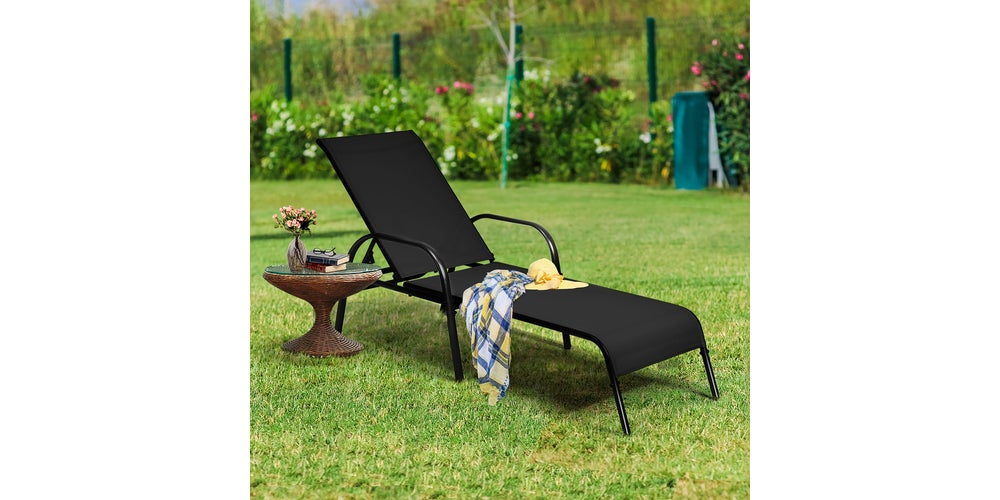 black patio chair with a brown table next to it on a green lawn