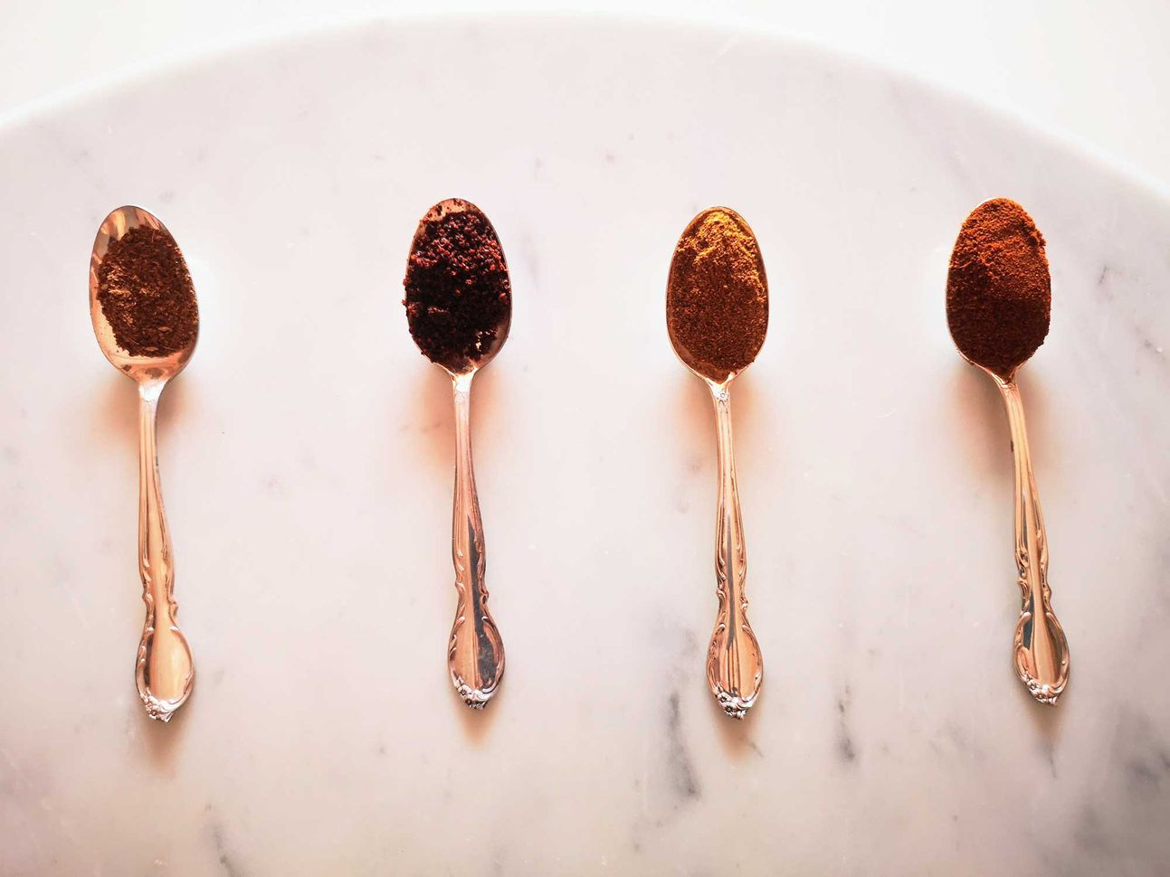 Four gold spoons with reddish spice blends on a marble table