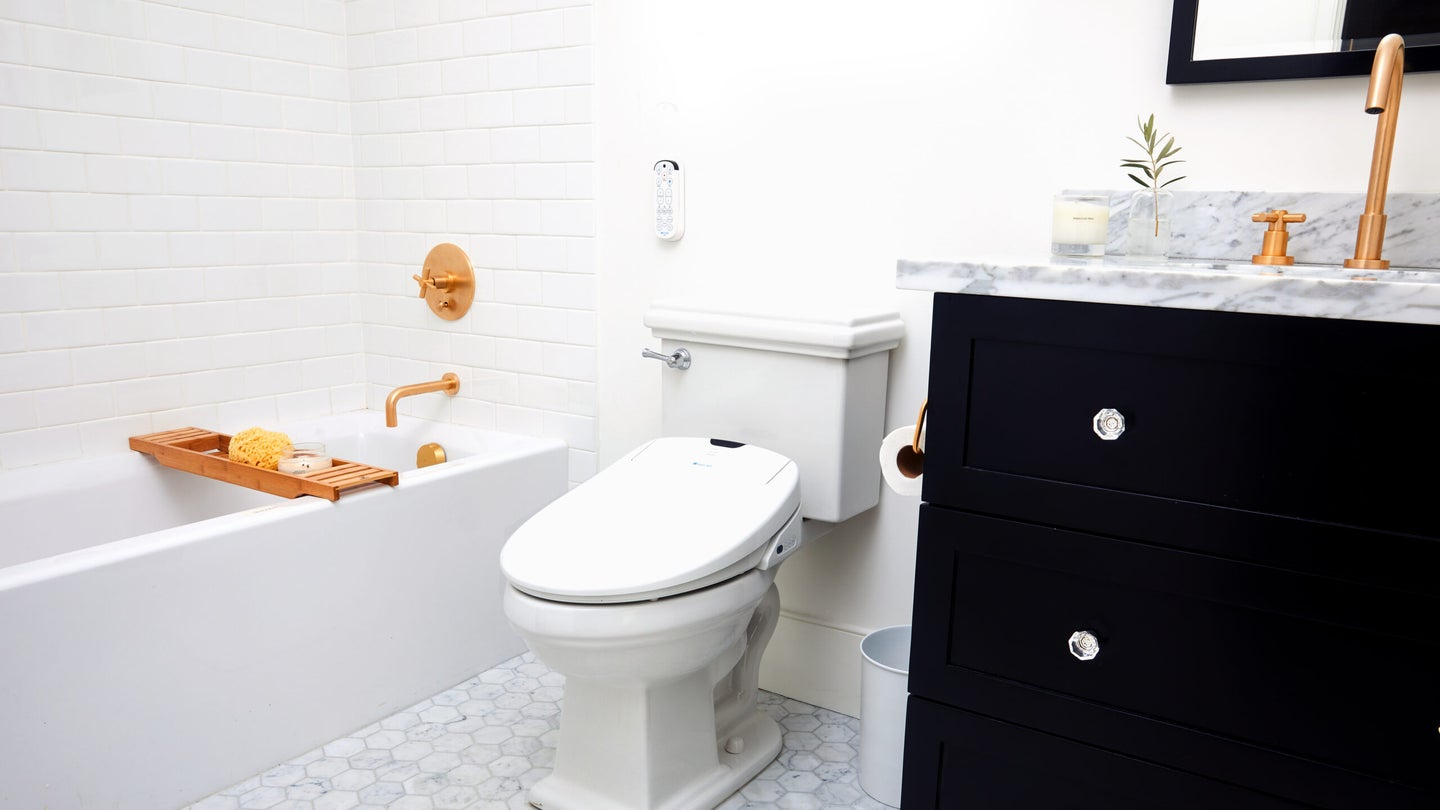 bidet attachment on a toilet next to a sink and bathtub
