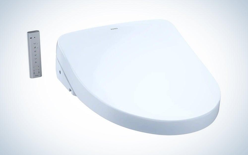 white toto electric bidet attachment with a remote