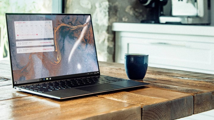 PC laptop on wooden table with a coffee mug beside it