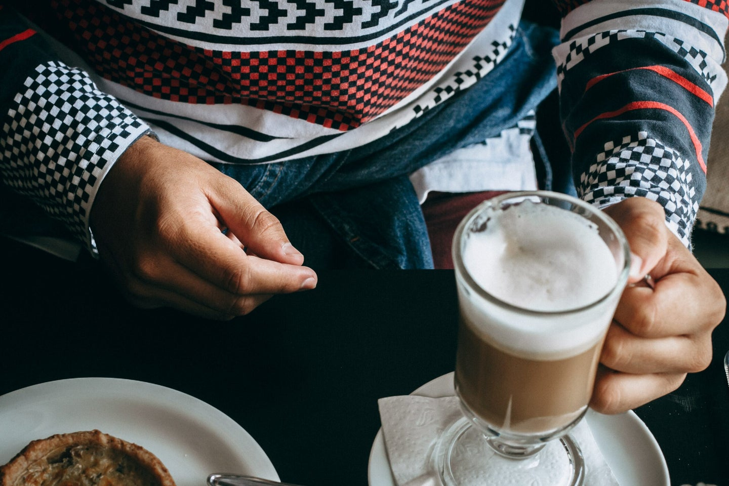 person in a sweater holding a coffee with foamed milk on top