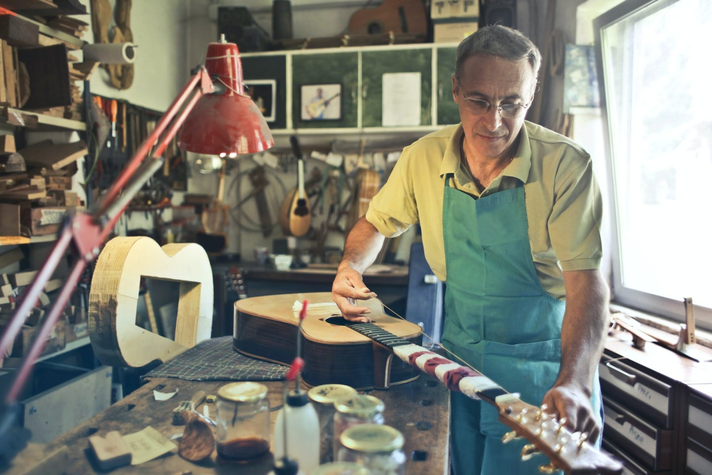 guy working on a guitar in a workshop