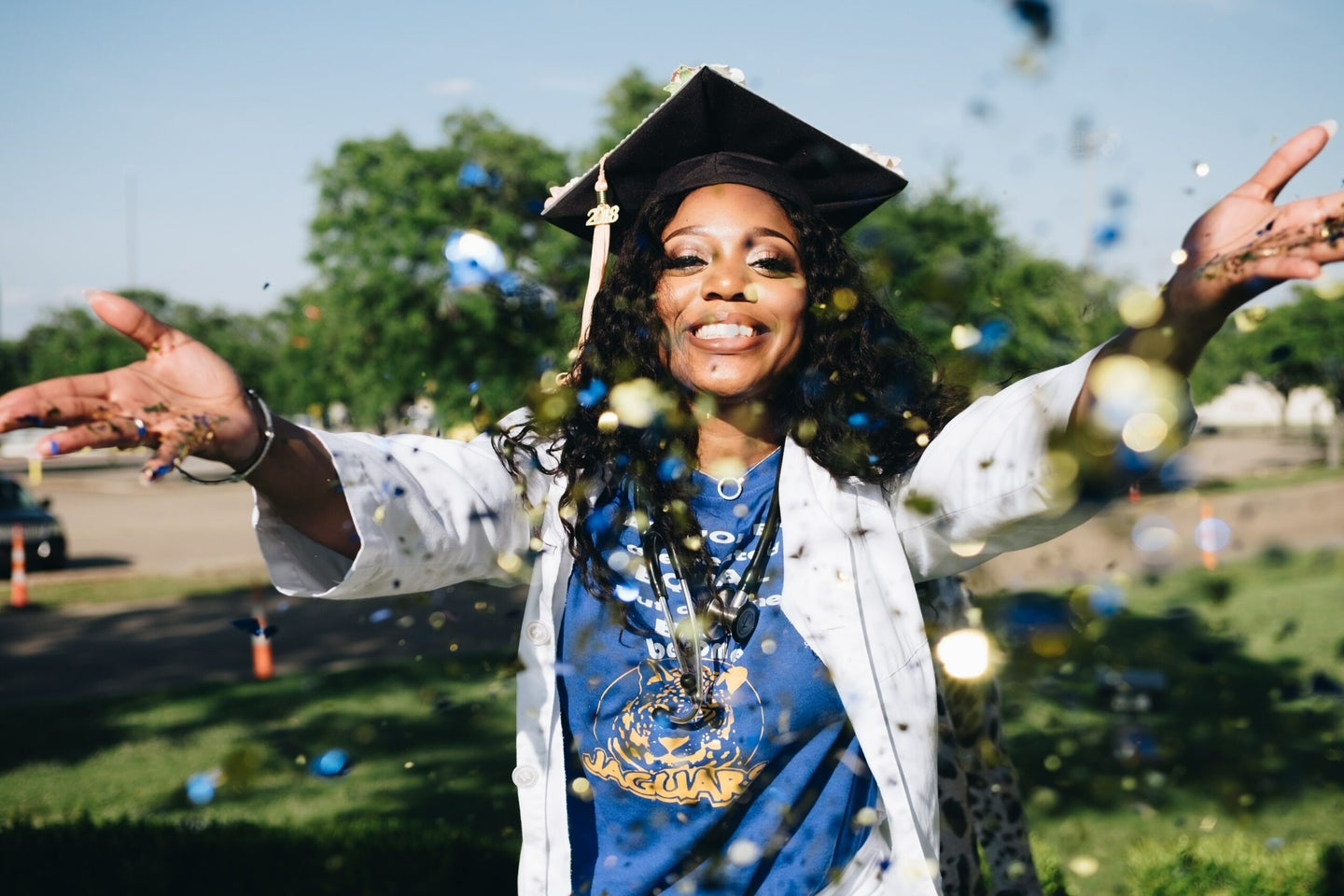 woman throwing glitter in front of herself wearing a graduation cap