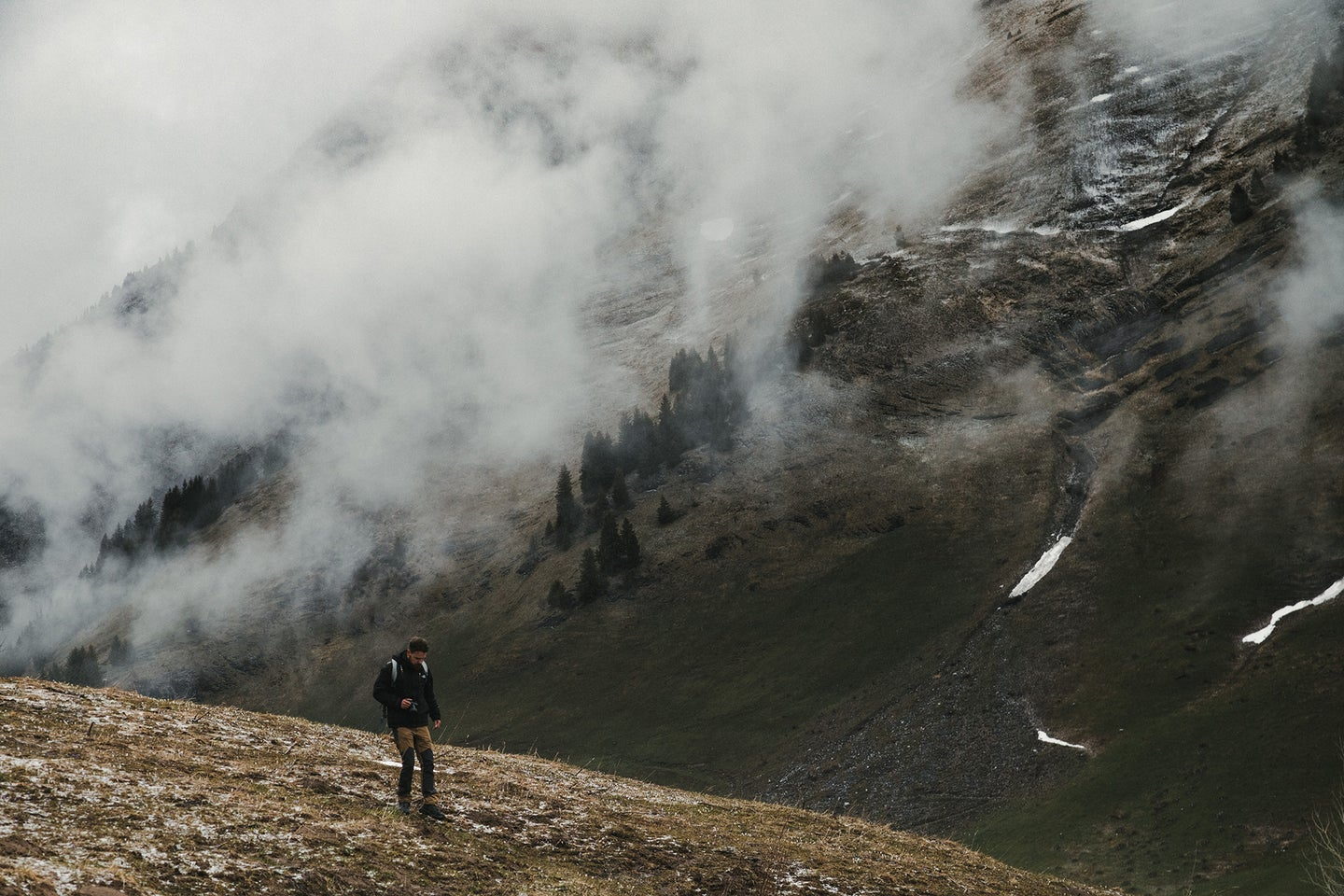 woman on a mountain with clouds above her