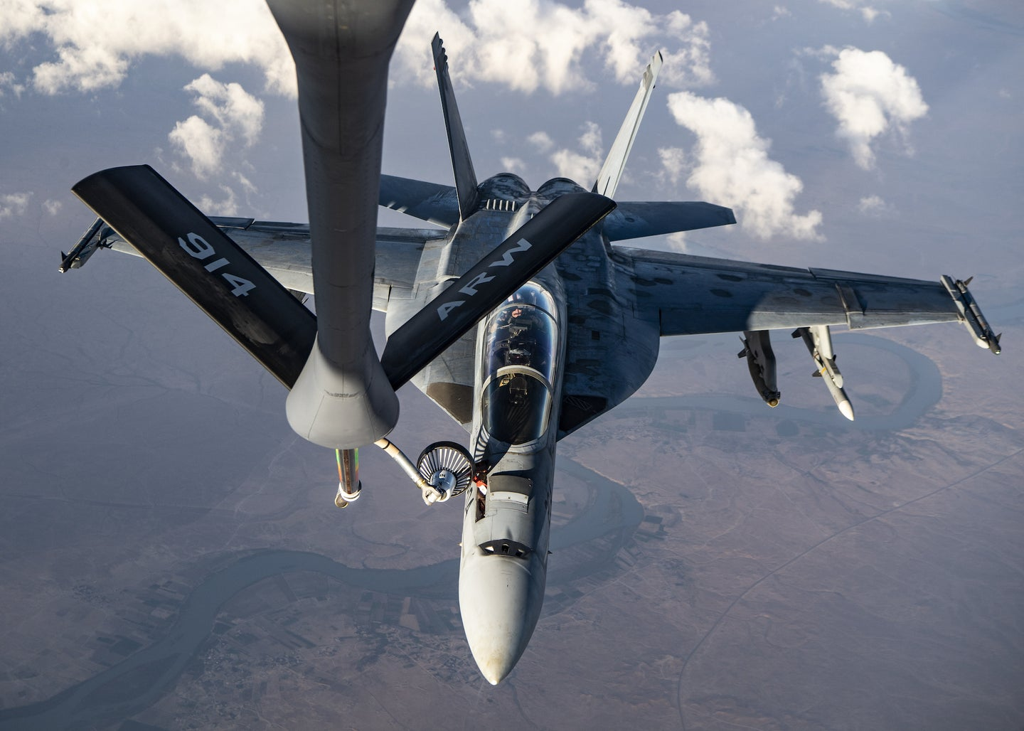 A F/A-18 Super Hornet is refueled the traditional way: by an aircraft with humans on board.