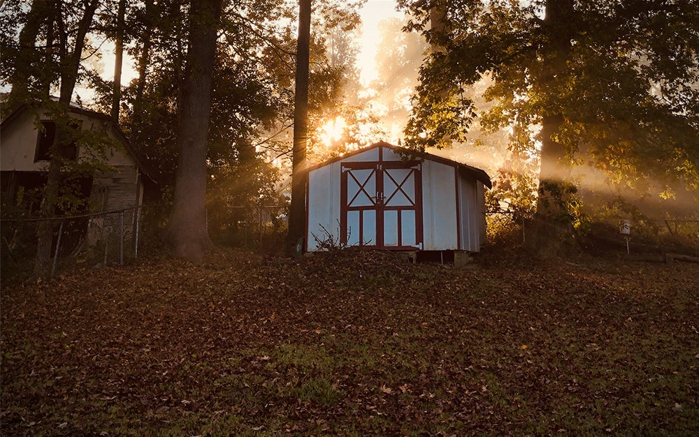 white storage shed with the sun rising behind it