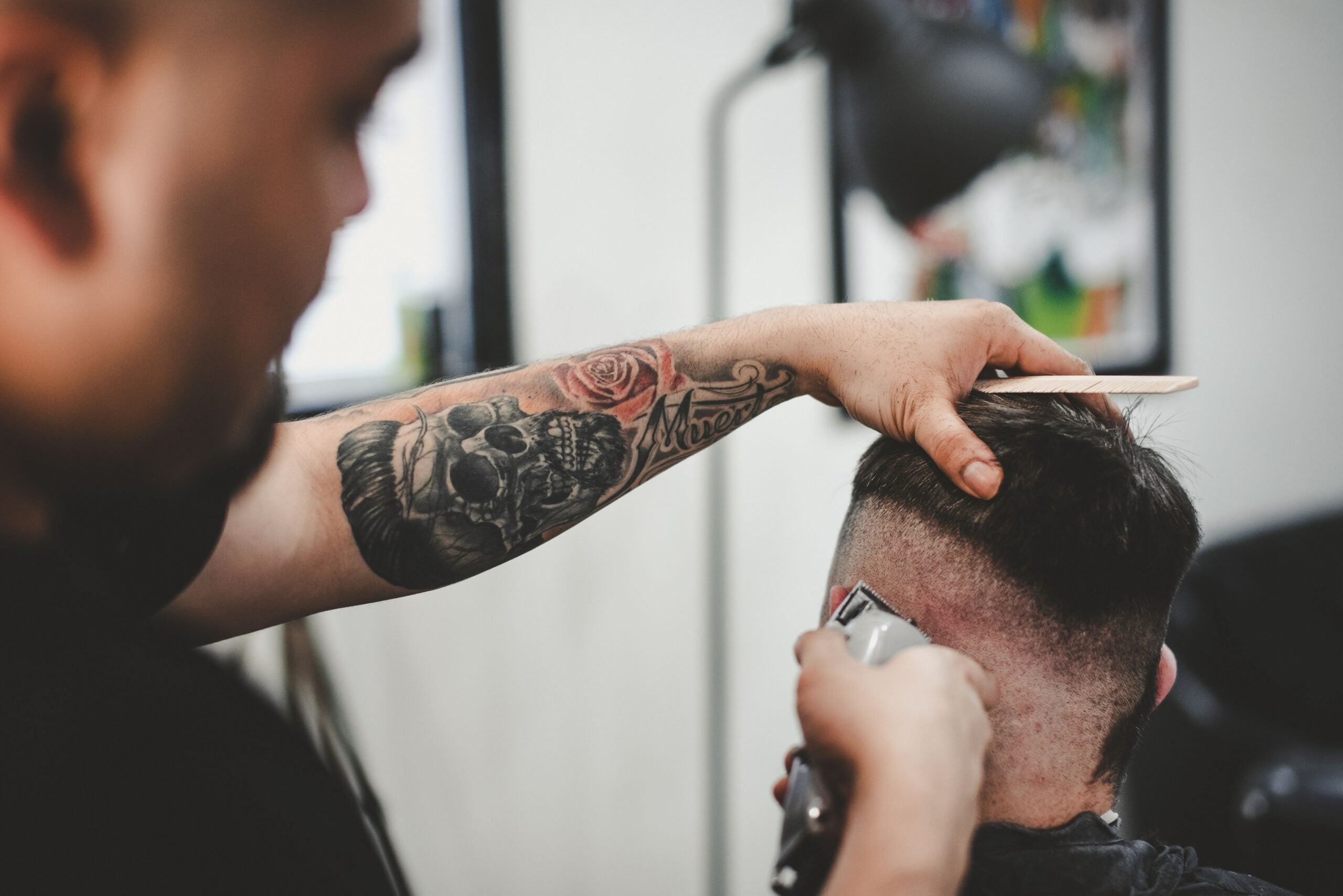 man with tattooed arms using clippers to cut another man's hair