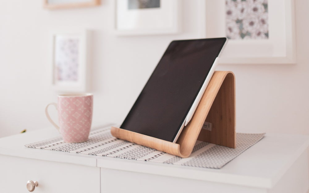 ipad on a wooden tablet stand next to a coffee mug