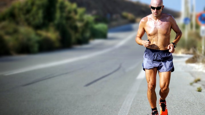 A man running shirtless on the side of a road in hot weather.