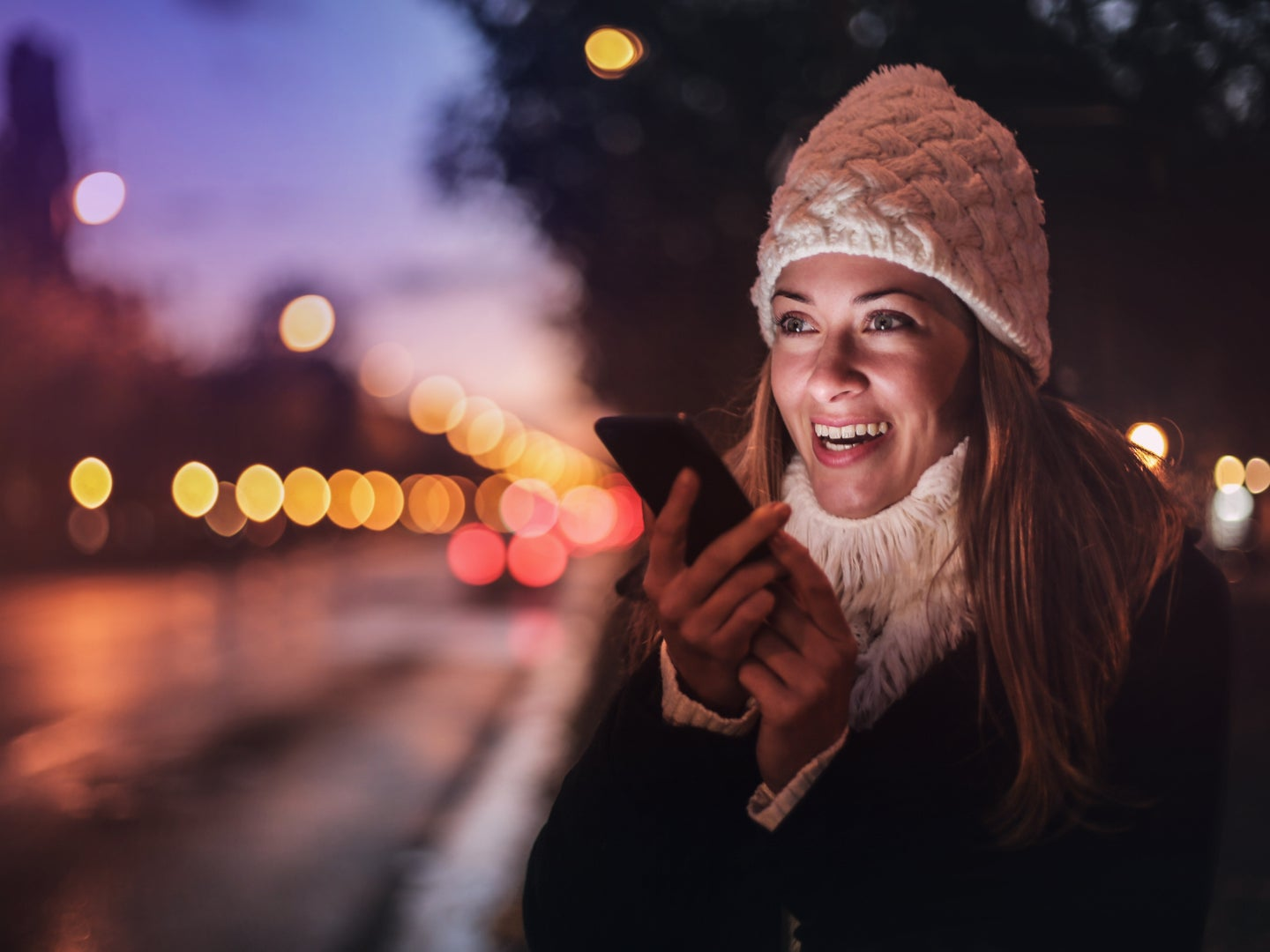 A woman wearing a white knit cap, a white sweater, and a jacket, talking into a phone at night by a street.