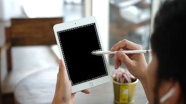 A person putting an Apple Pencil on a blank iPad Mini screen.