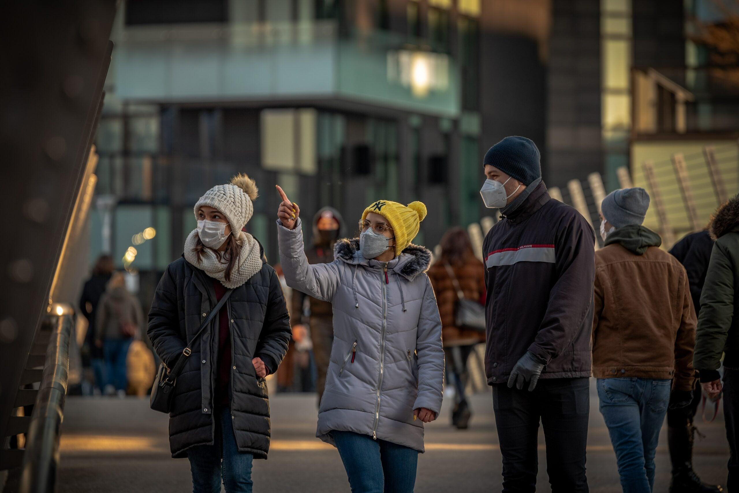 people wearing masks walking down a street