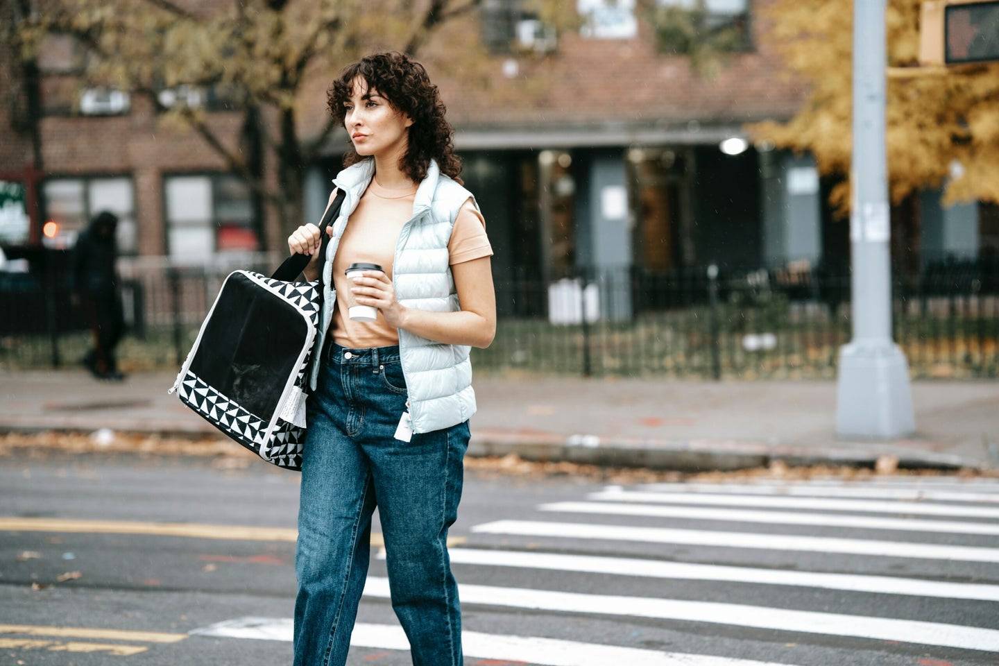 woman walking on street with a pet carrier
