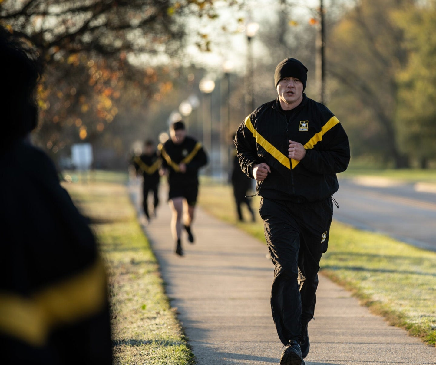 Army cadet running in a black and yellow sweatsuit on a sidewalk