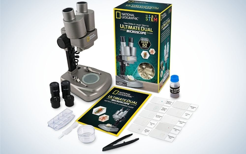 Grey National Geographic Microscope with black small lens and with instructions paper on it.