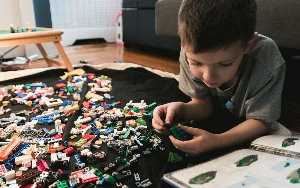 Thinking kid trying to form different size and colored puzzle.