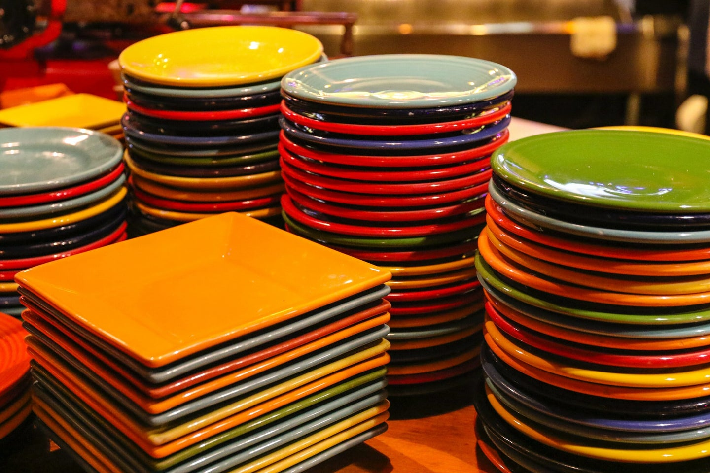 round and square plates of every color stacked on a table