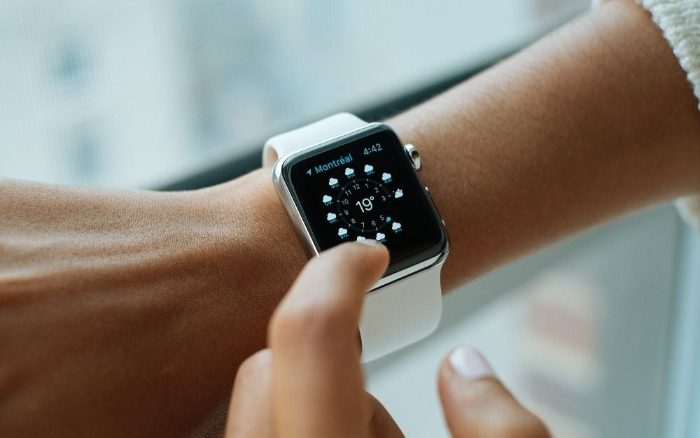 A white apple watch with a silver case