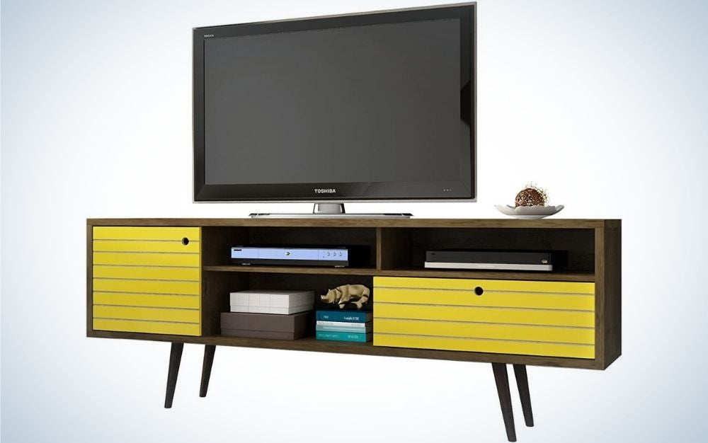 Black Tv standing on a modern TV stand with sprayed legs with three shelves which two of them are yellow wood shelves, one cabinet and one drawer.