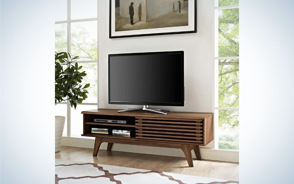A painting hung on the white wall and a large led TV standing on a wooden laminate tv stand.
