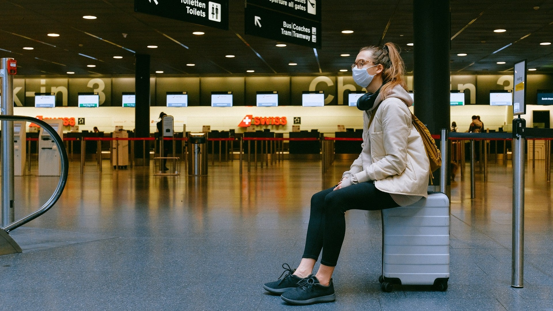 Traveler sits on suitcase in airport.