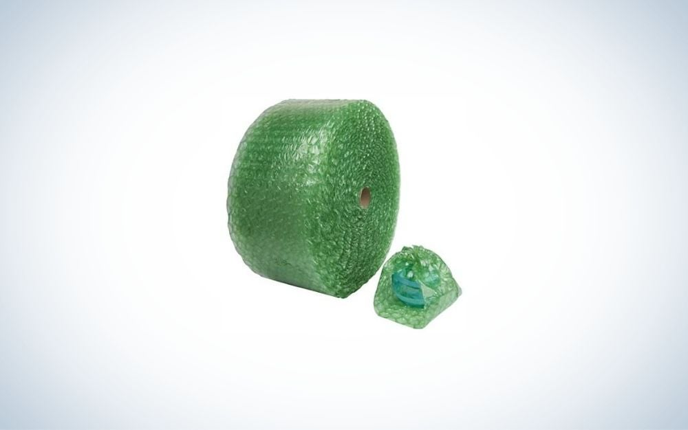 Green bubble wrap roll and a cup covered by the wrap