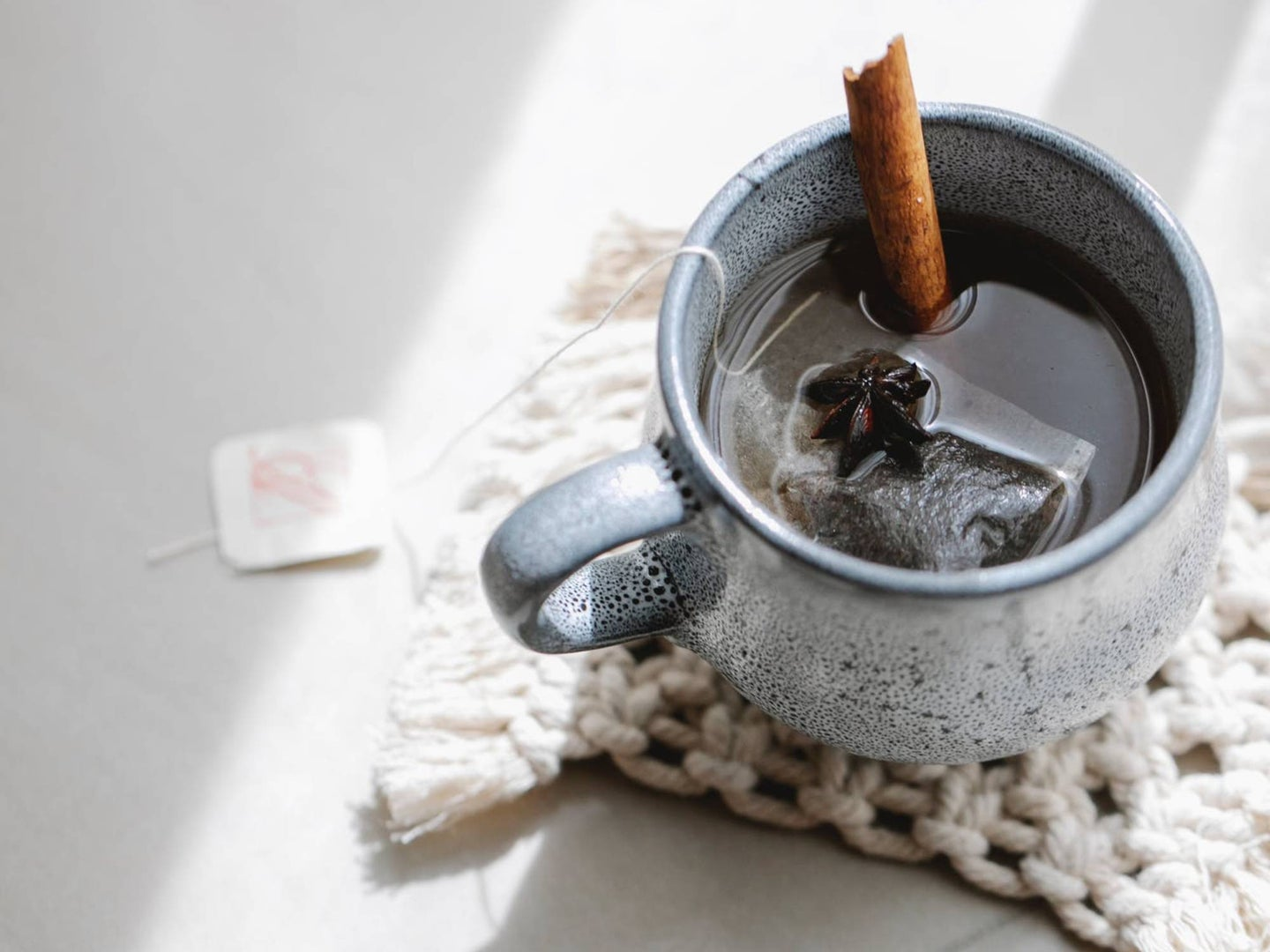 A cup of tea with a cinnamon stick in it