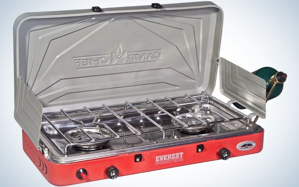 A grey Camp Chef burner stove with two hobs and a red color underneath.
