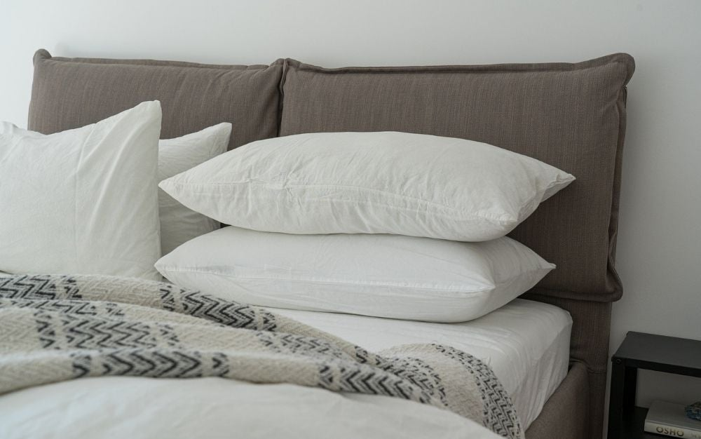 4 big white pillows laying on a memory foam mattress topper