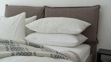 4 big white pillows laying on a memory foam mattress topper