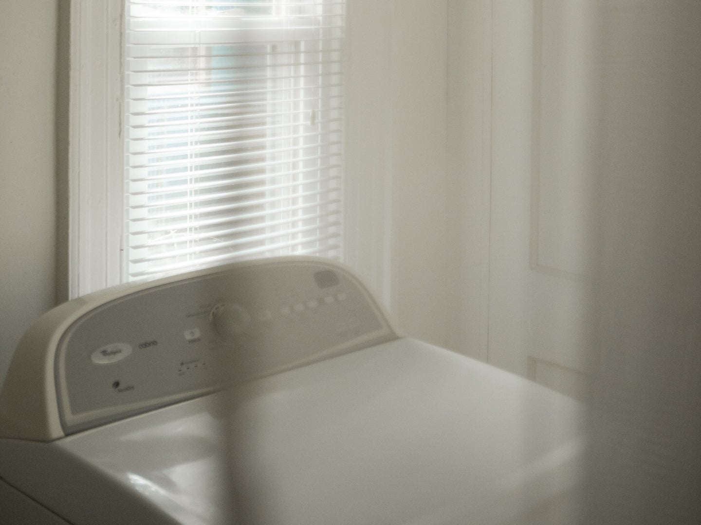 A white clothes dryer behind a white curtain, in front of a tall window with sunlight shining through.