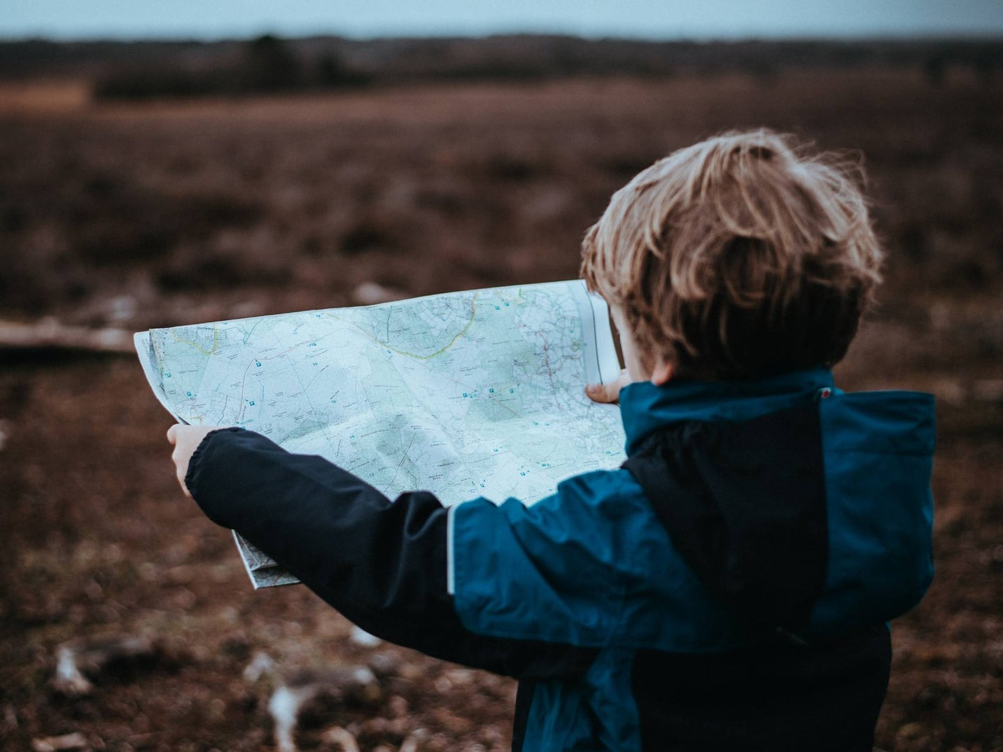 A child holding a map outdoors.