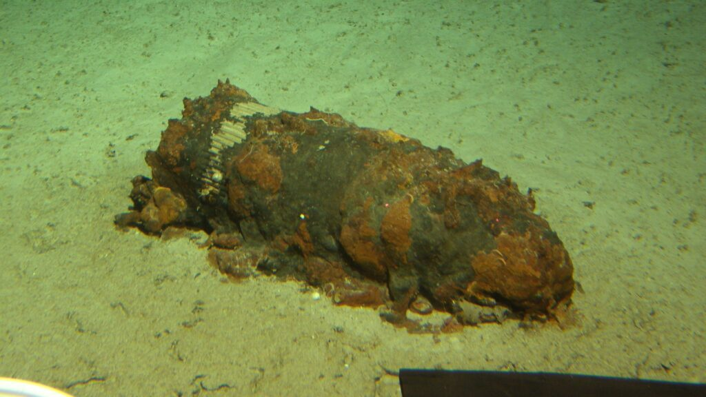 A corroded chemical munition sits at the bottom of the sea.