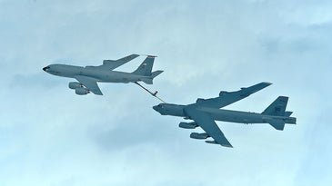 A bomber is refueled behind a tanker airplane.