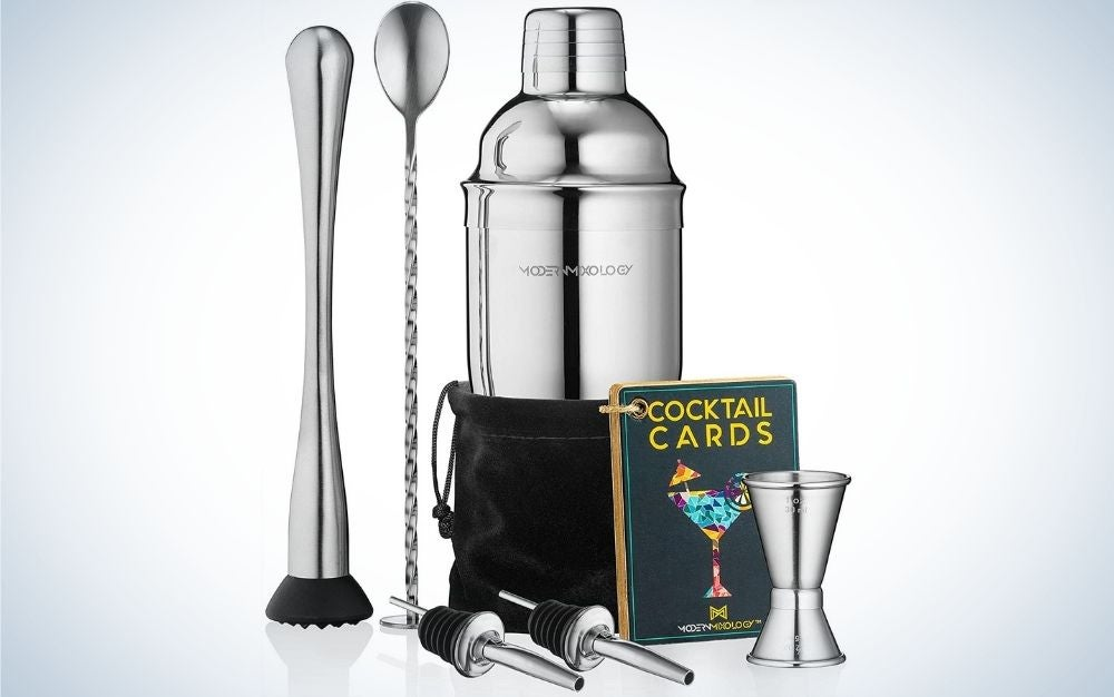 A silver cocktail shaker set drink mixer with portable Bartender Kit with 24oz Martini shaker bar tool set, 2 pourers, muddler, jigger, mixing spoon and velvet bag in front of it.