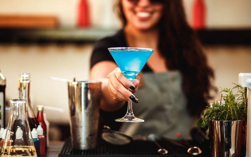 A smiley girl that has in her hands a sky color cocktail beside a silver shaker cocktail glass.
