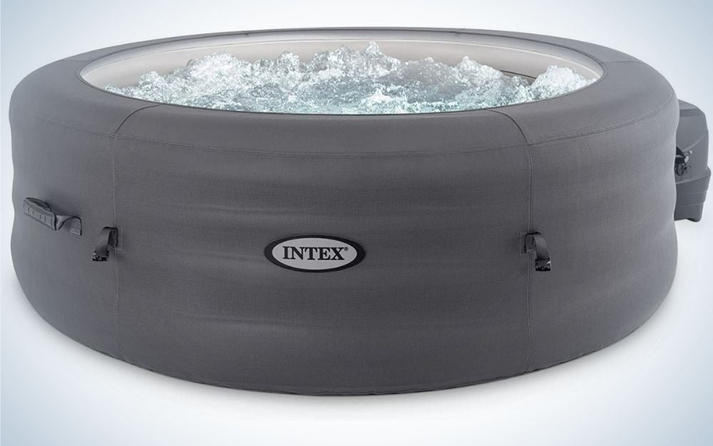 A black Intex outdoor portable inflatable round heated hot tub spa with bubble water inside of it.