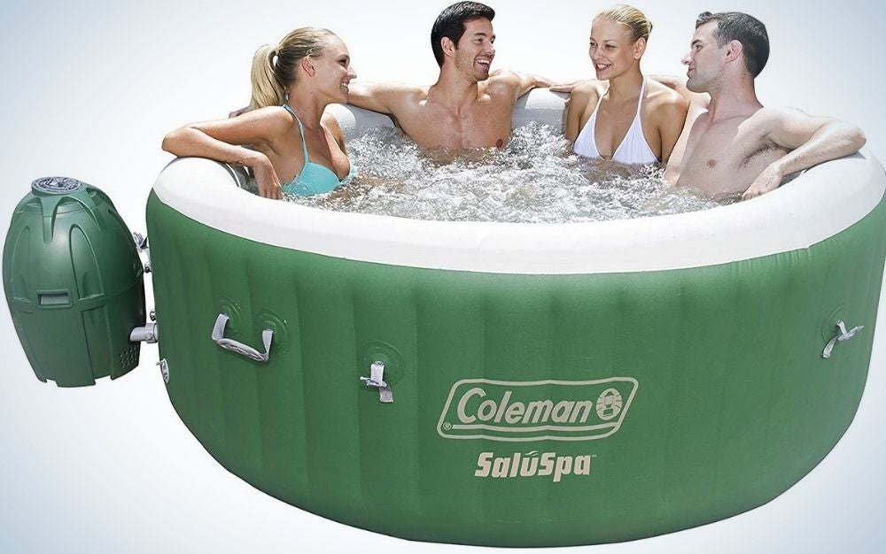 Two women and two men in a green portable Coleman SaluSpa talking and resting with each other.