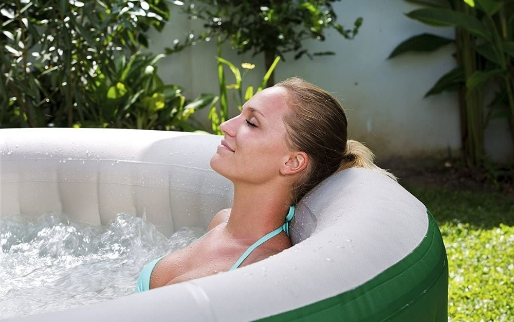 A girl smiling and relaxing with her eyes closed inside a outdoor portable hot tub spa.