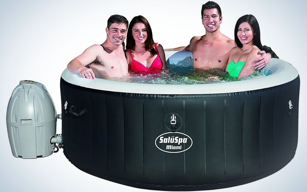 Four persons inside the black SaluSpa Miami inflatable hot tub connected to a small grey sphere-shaped deposit on the side of the tube.